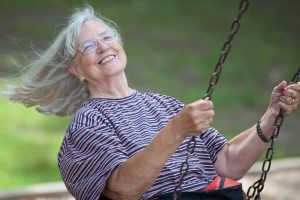 Older white woman swinging on a swing.