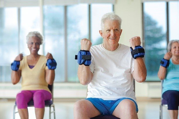 elderly participants seated in chairs with weights on wrists bending arms