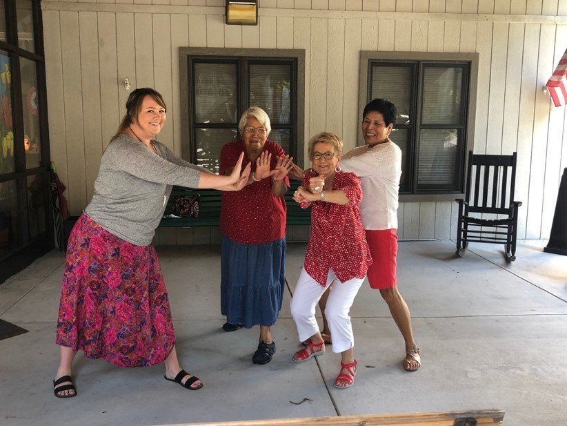 three women, 69, 73, 76 participating in Tai Chi for Arthritis and Fall Prevention at Tsali Manor Senior Center with instructor helping