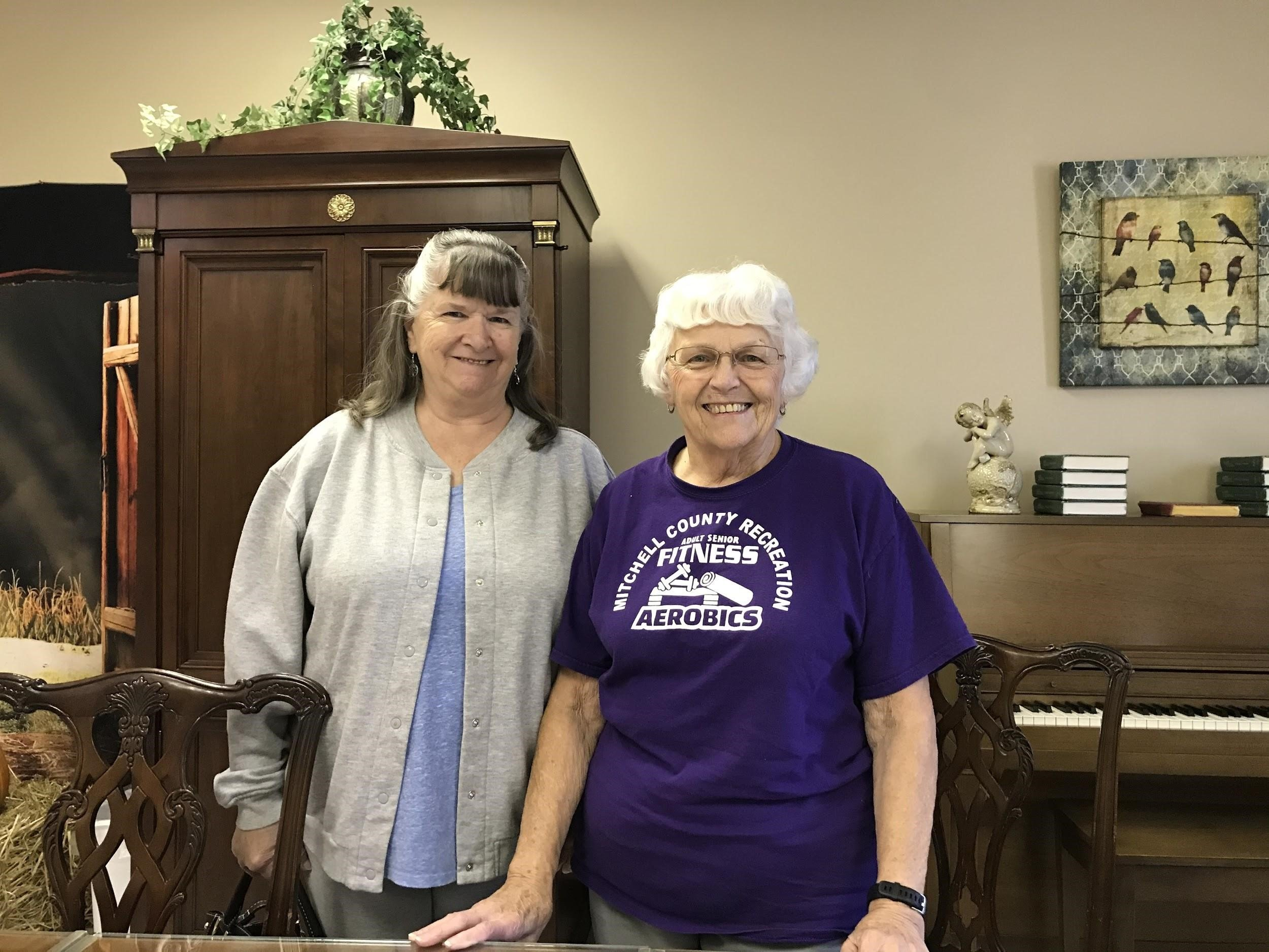 two white elderly woman standing in front of a piano at the senior center